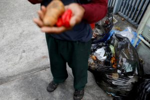 FILE PHOTO: A man holds vegetables after he scavenges for food in a rubbish bin in Caracas, Venezuela February 27, 2019. REUTERS/Carlos Jasso/File Photo