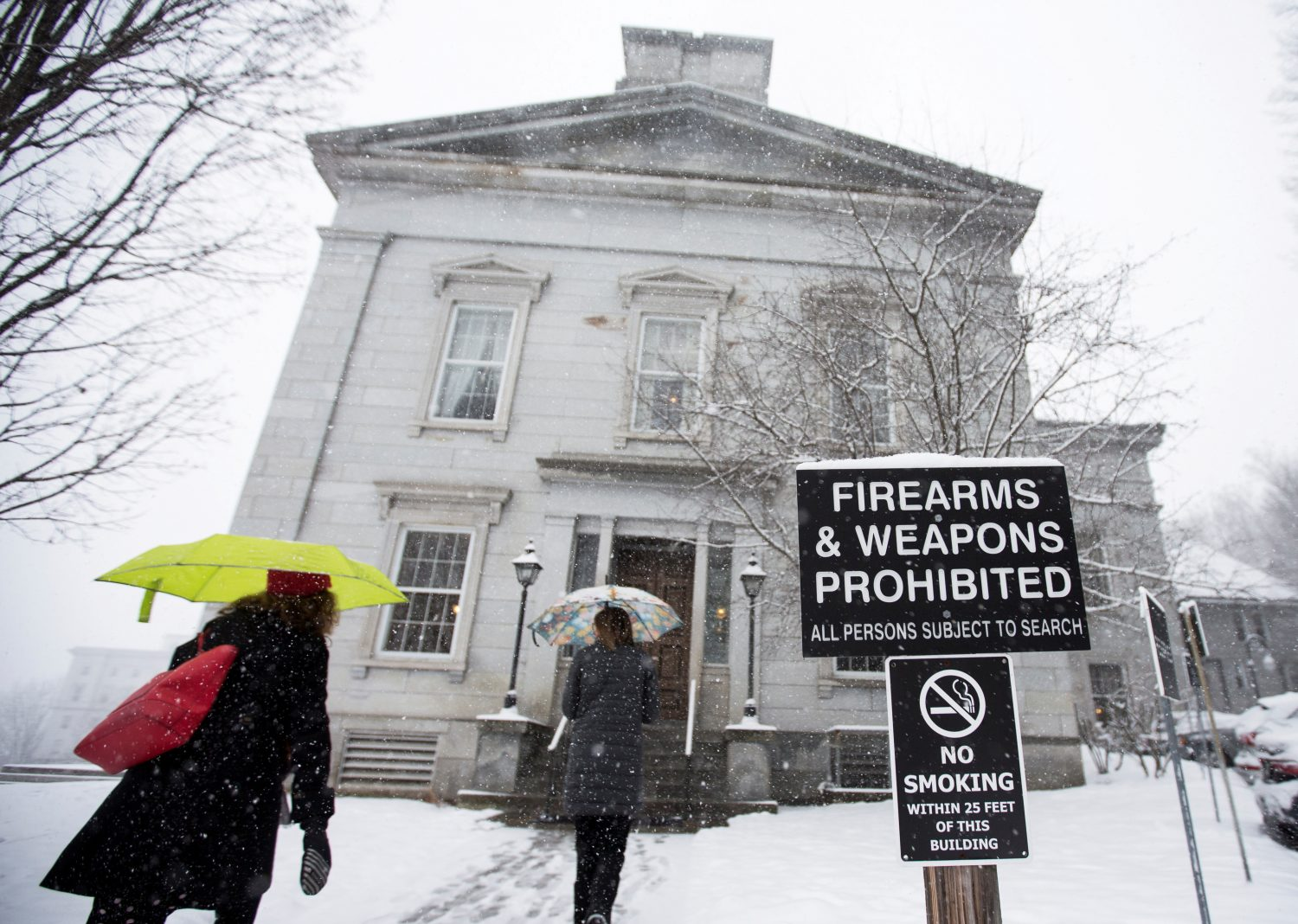FILE PHOTO: People walk past a sign prohibiting firearms and weapons inside the State Legislature in Montpelier, Vermont, U.S., March 13, 2018. REUTERS/Christinne Muschi