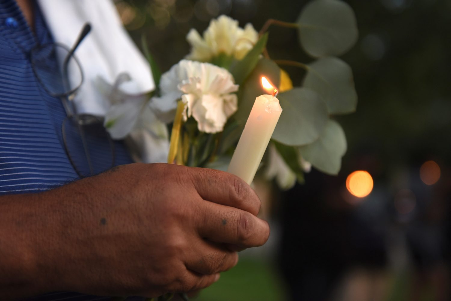 A man holds flowers and a candle as people gather for a vigil following Saturday's shooting in Odessa, Texas, U.S. September 1, 2019. REUTERS/Callaghan O'Hare