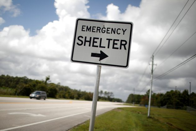 "FILE PHOTO: An ""Emergency shelter"" sign points to the Pedro Menendez High School ahead of the arrival of Hurricane Dorian in St. Augustine, Florida, U.S., September 2, 2019. REUTERS/Marco Bello - RC1823A64B90/File Photo"