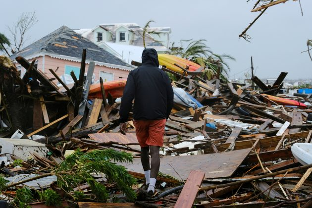 FILE PHOTO: A man walks through the rubble in the aftermath of Hurricane Dorian on the Great Abaco island town of Marsh Harbour, Bahamas, September 2, 2019. REUTERS/Dante Carrer
