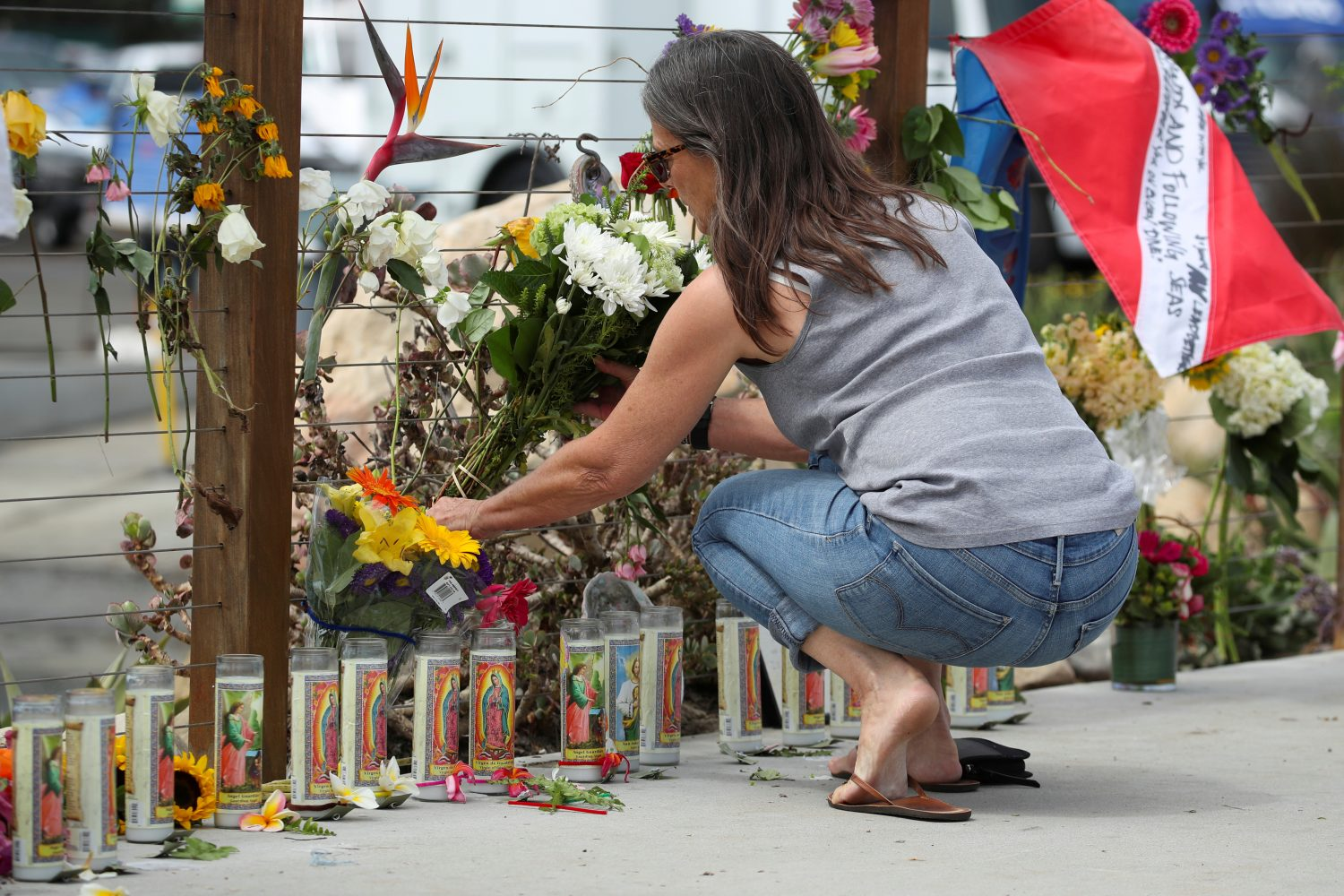 FILE PHOTO: A woman places flowers at a makeshift memorial near Truth Aquatics as the search continues for those missing in a pre-dawn fire that sank a commercial diving boat near Santa Barbara, California, U.S., September 3, 2019. REUTERS/Mike Blake/File Photo