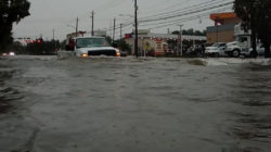 A car passes through a flooded street as storm Imelda hits Houston, Texas, U.S., September 19, 2019 in this screen grab obtained from social media video. @kingjames.daniel/via REUTERS