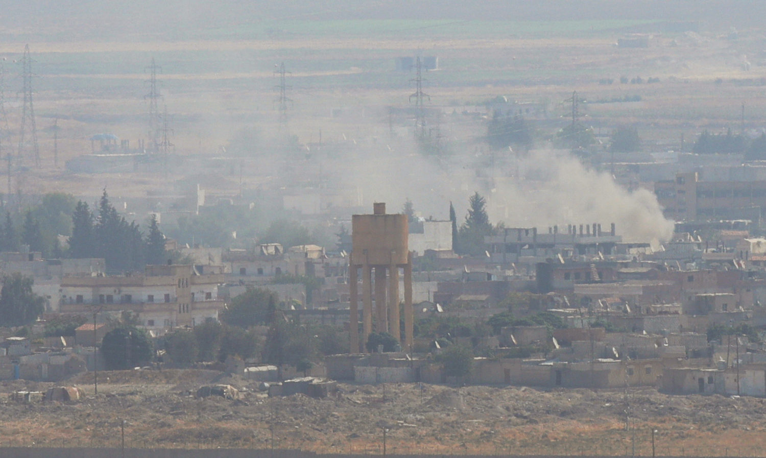 Smoke rises over the Syrian town of Ras al-Ain as seen from the Turkish border town of Ceylanpinar, Sanliurfa province, Turkey, October 18, 2019. REUTERS/Stoyan Nenov