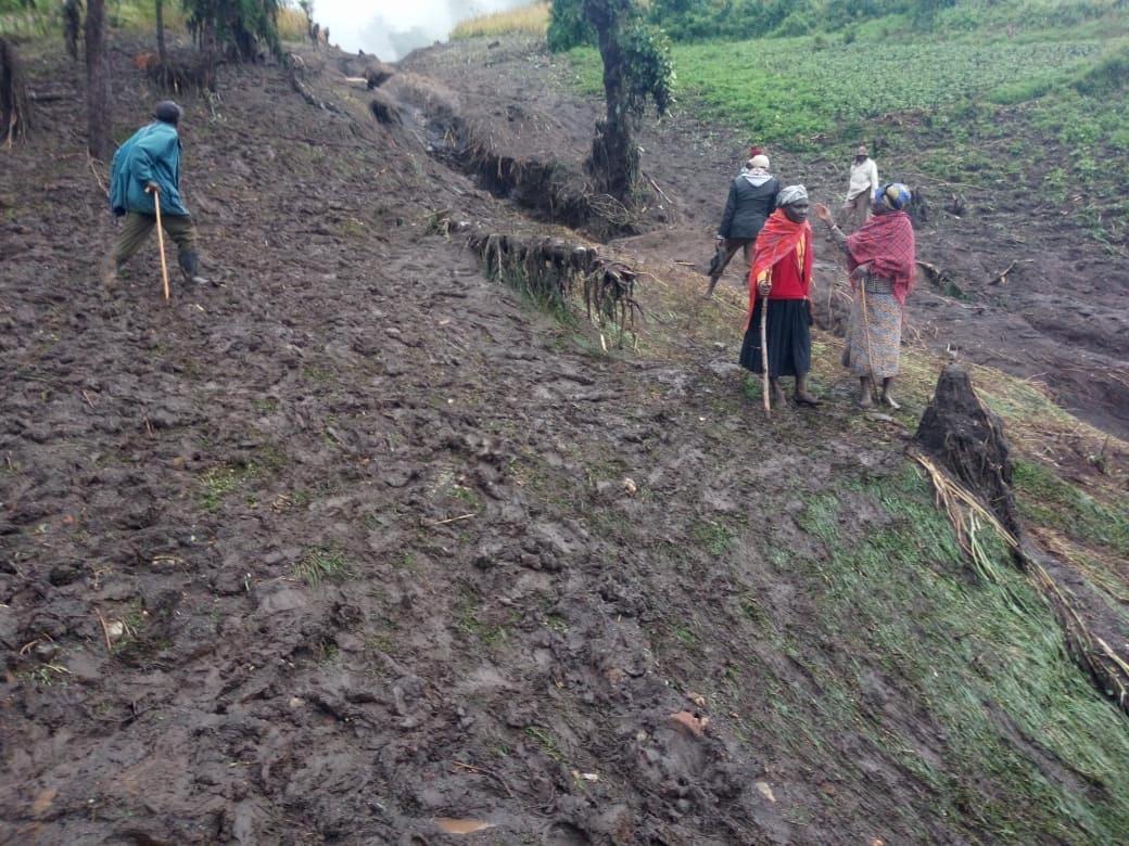 People walk in the mud after heavy rains caused landslides in the village of Parua, West Pokot County, Kenya November 23, 2019. REUTERS/Moses Lokeris